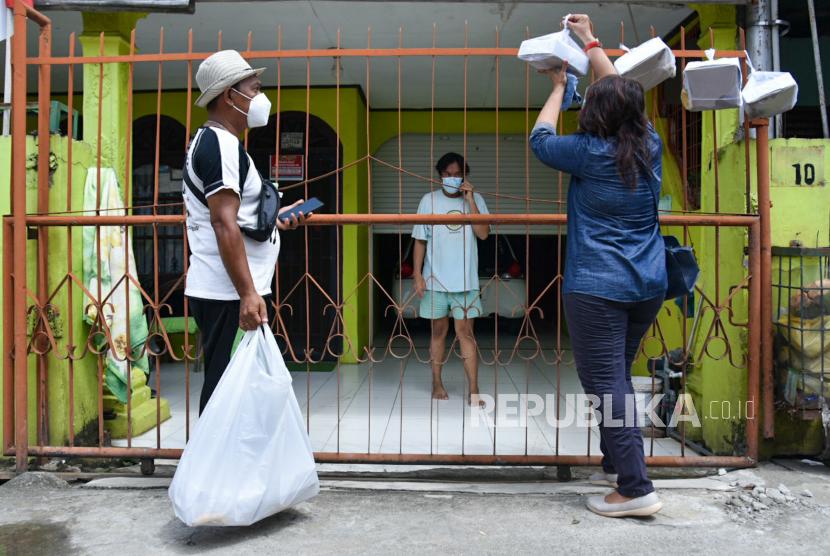 Relawan bersama kepala lingkungan menggantung bantuan makanan di pagar warga yang menjalani isolasi mandiri (isoman).