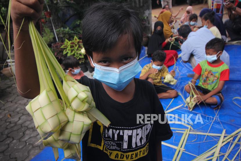 Seorang anak menunjukkan cangkang ketupat anyamannya usai belajar membuat cangkang ketupat di Surabaya, Jawa Timur, Rabu (19/5/2021). Dinkes Surabaya mengonfirmasi bahwa saat ini banyak anak-anak di Kota Surabaya yang terkonfirmasi positif Covid-19. (ilustrasi)