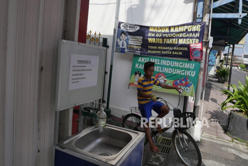 Spanduk imbauan aturan protokol kesehatan Covid-19 terpasang di pintu masuk kampung di Yogyakarta.