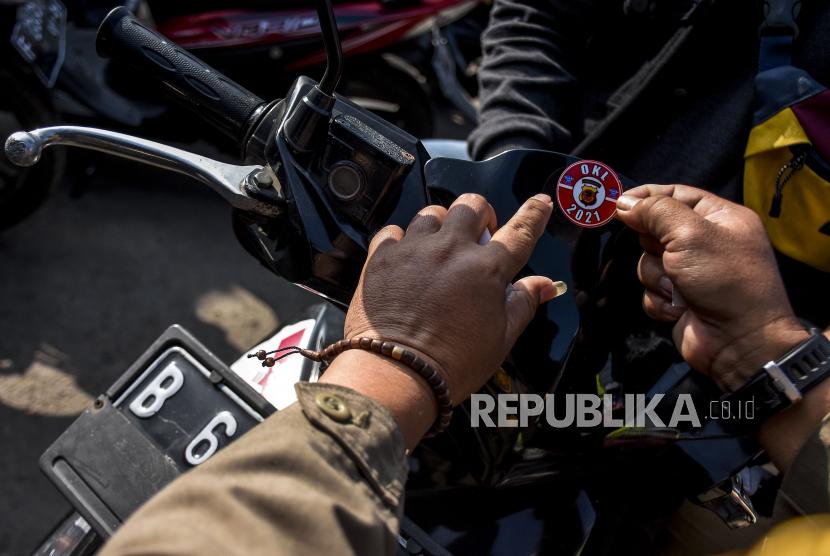 Petugas Satpol PP Kabupaten Bandung Barat menempelkan stiker ke kendaraan dengan plat nomor dari luar Bandung , (ilustrasi).
