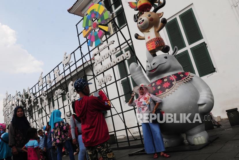 Sejumlah wisatawan berfoto dengan patung maskot Asian games di Kota Tua, Jakarta, Ahad (17/6).