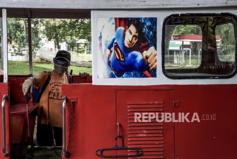 Petugas menyemprotkan cairan disinfektan di salah satu wahana permainan di Taman Lalu Lintas, Kota Bandung, Senin (29/3/2021).