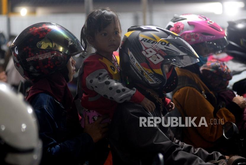 Pemudik sepeda motor yang membawa anaknya mengantri memasuki kapal di Pelabuhan Merak ,Banten, Selasa (12/6) dini hari.