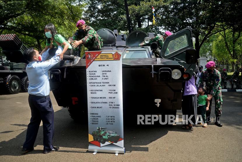 Warga menaiki kendaraan alat utama sistem senjata (alutsista) milik TNI yang dipamerkan dalam rangka HUT TNI ke-76 di depan Istana Merdeka, Jakarta, Selasa (5/10). Tema yang diangkat pada peringatan HUT TNI tahun ini adalah Bersatu, Berjuang, Kita Pasti Menang.Prayogi/Republika