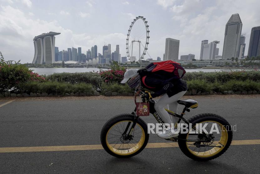 Seorang pengendara sepeda bersepeda melewati cakrawala distrik keuangan melintasi Gardens by the Bay East di Singapura, 15 Februari 2021. Singapura sedang menyusun peta jalan tentang bagaimana hidup lebih normal dengan Covid-19. Ilustrasi.