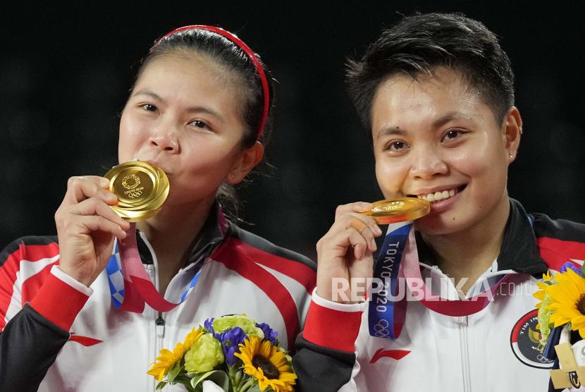 Greysia Polii, kiri, dan Apriyani Rahayu merayakan dengan medali emas mereka setelah mengalahkan Chen Qing Chen dan Jia Yi Fan dari China dalam pertandingan perebutan medali emas ganda putri di Olimpiade Musim Panas 2020, Senin, 2 Agustus 2021, di Tokyo, Jepang.
