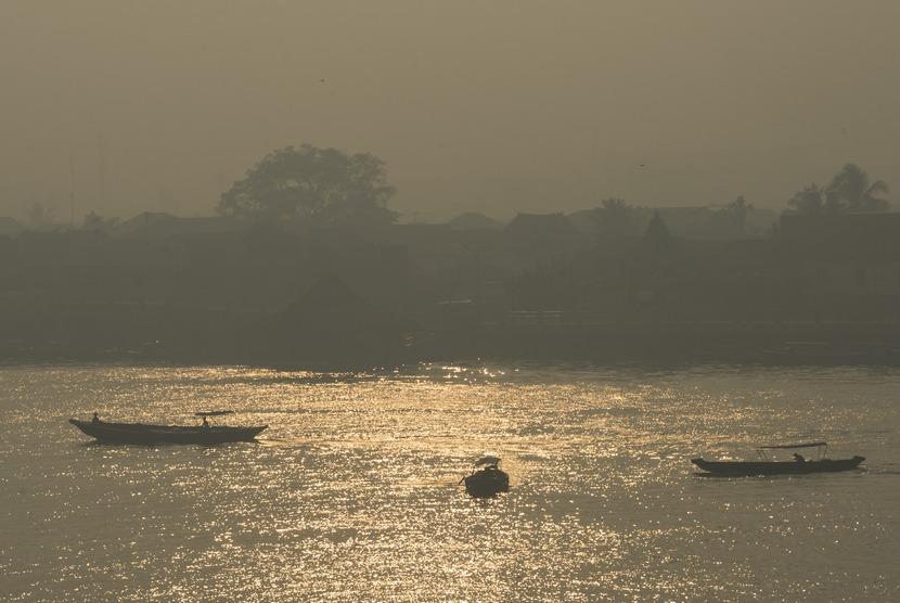 Kapal melintas di Sungai Musi yang masih tertutup kabut asap, Palembang, Sumatera Selatan, Selasa (4/11).   (Antara/Rosa Panggabean)