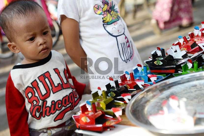 Seorang anak mengamati mainan perahu-perahuan di Jakarta.