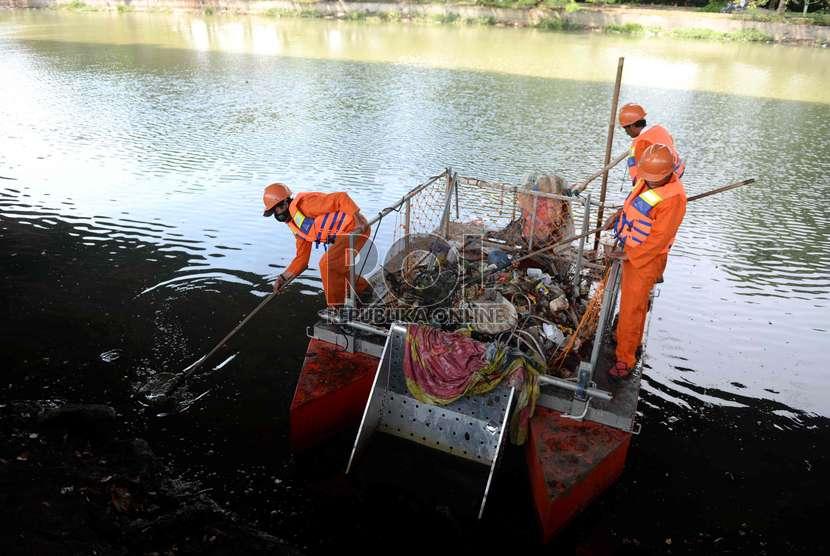 Petugas kebersihan memungut sampah plastik di sungai (ilustrasi)