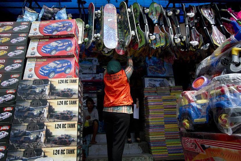 Petugas Standardisasi dan Perlindungan Konsumen Kementerian Perdagangan memeriksa label SNI (Standar Nasional Indonesia) pada mainan anak yang dijual di Pasar Gembrong, Jakarta, Rabu (10/12).(Antara/Rosa Panggabean)