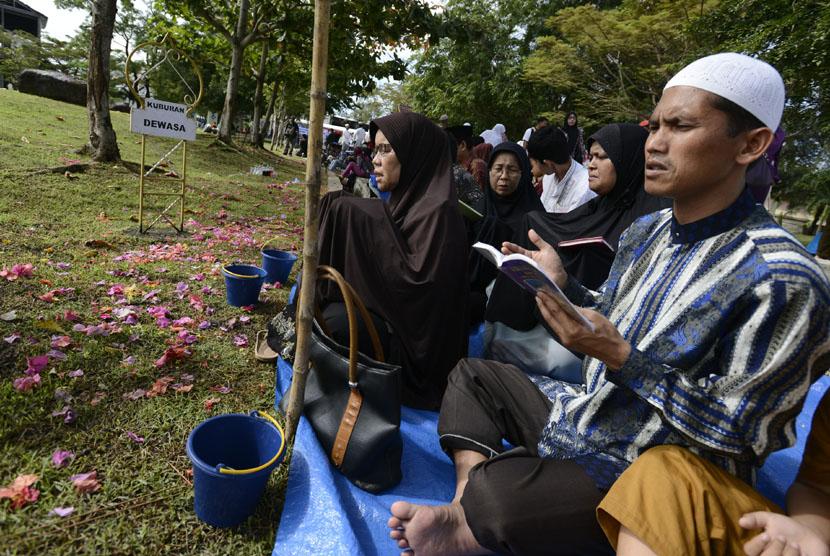 Warga memanjatkan doa di pemakaman massal korban tsunami (ilustrasi)