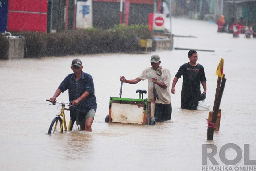 Warga melintasi banjir di Andir, Dayeuhkolot, Kabupaten Bandung, Ahad(28/12). (foto : Septianjar Muharam)