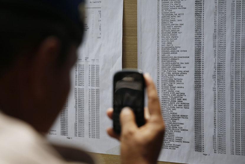Seorang pria memotret daftar nama penumpang pesawat AirAsia QZ 8501 di Bandara Internasional Juanda, Surabaya, Senin (29/12).