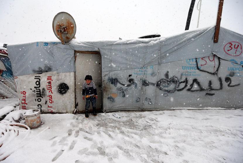 Seorang anak berdiri di depan tenda kamp pengungsi asal Suriah di desa Deir Zannoun, lembah Bekaa, Lebanon, Rabu (7/1). (AP/Hussein Malla)