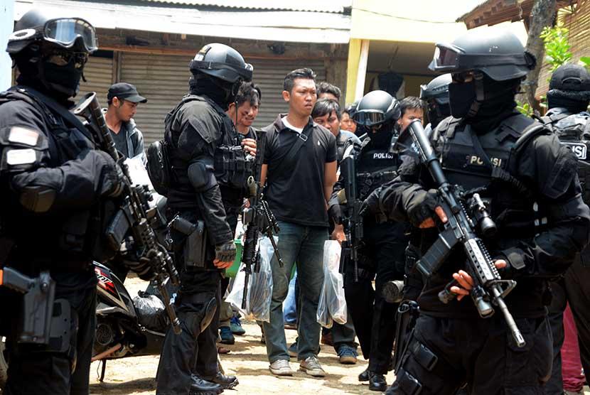 Personil Densus 88 Antiteror Mabes Polri  mengawal petugas yang membawa barang bukti usai melakukan penggeledahan di kediaman Tuah Febriwansyah   yang diduga terlibat dalam jaringan ISIS di Setu, Tangerang Selatan, Banten, Ahad (22/3).