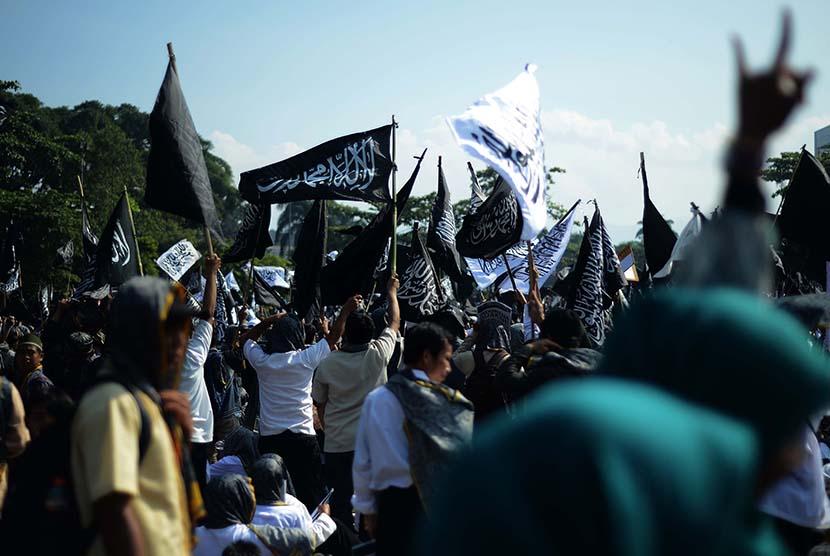 Sejumlah masa yang tergabung dalam Hizbut Tahrir Indonesia (HTI) mengacungkan poster saat rapat dan pawai akbar (RPA) 2015 dengan tajuk Bersama Umat Tegakkan Khilafah di Lapangan Gasibu, Kota Bandung, Kamis (14/5). (foto : Septianjar Muharam)
