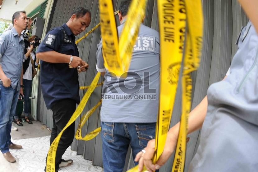 Petugas Polda Metro Jaya memasang garis polisi saat penggeledahan rumah toko milik bos investasi tisu bodong di Jalan Boulevard Raya Blok WE2, no 2B, Kelapa Gading, Jakarta Utara, Jumat (5/6). (Republika/Agung Supriyanto)