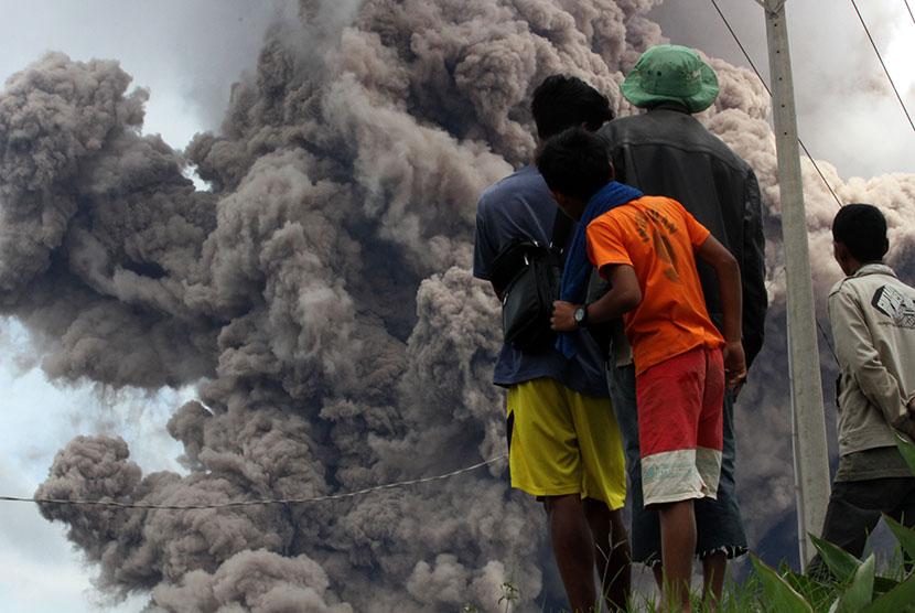 Sejumlah warga melihat Gunung Sinabung menyemburkan material vulkanis disertai awan panas, di Desa Namanteran, Karo, Sumatera Utara, Selasa (16/6).  (Antara/Irsan Mulyadi)