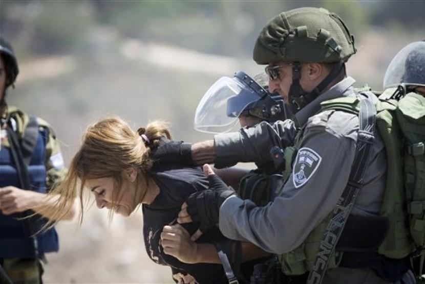 Tentara Israel menahan seorang wanita Palestina.