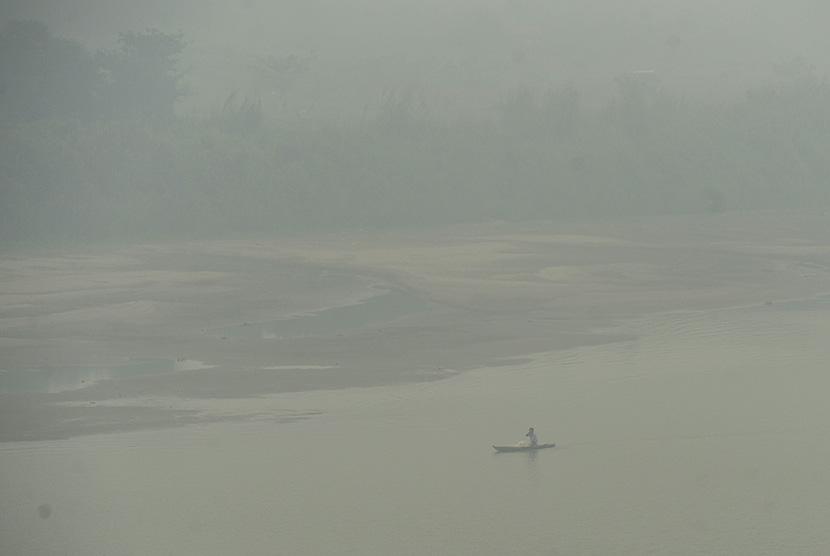 Seorang nelayan mengarungi Sungai Batanghari yang tertutup kabut asap di Jambi, Rabu (9/9).  (Antara/Wahyu Putro A)
