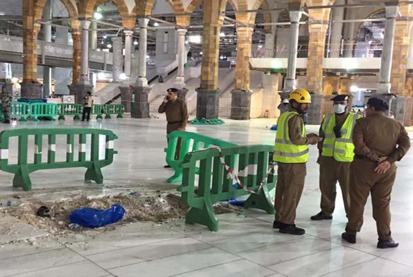Polisi Arab Saudi berjaga di lokasi jatuhnya crane di area Masjidil Haram, Jumat (11/9).