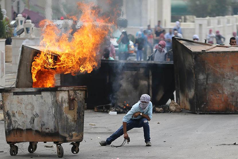 Pengunjuk Palestina bentrok dengan pasukan Israel dekat pemukiman yahudi Bet El, Ramallah, Palestina, Sabtu (10/10).  (REUTERS/Mohamad Torokman)