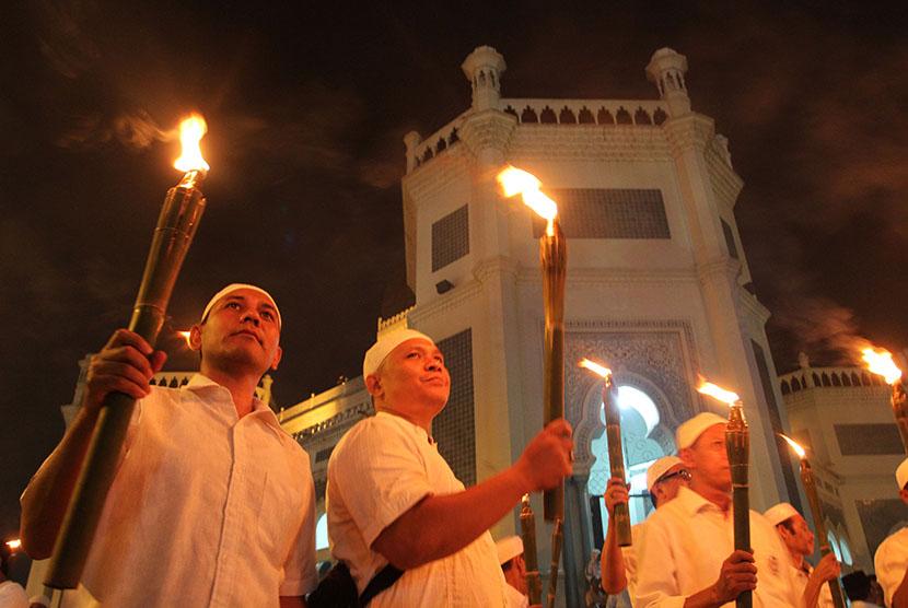 Umat Muslim memegang obor ketika mengikuti pawai dari Masjid Raya Al Mashun menuju Masjid Agung, Medan, Sumatera Utara, Selasa (13/10) malam.  (Antara/Irsan Mulyadi)