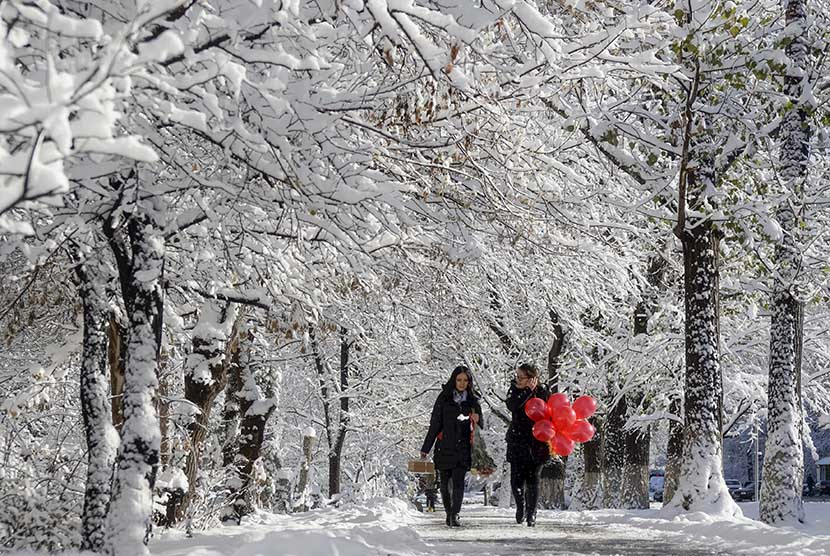 Warga melintasi jalan yang diselimuti salju putih di Almaty, Kazakhstan.  (Reuters//Shamil Zhumatov)