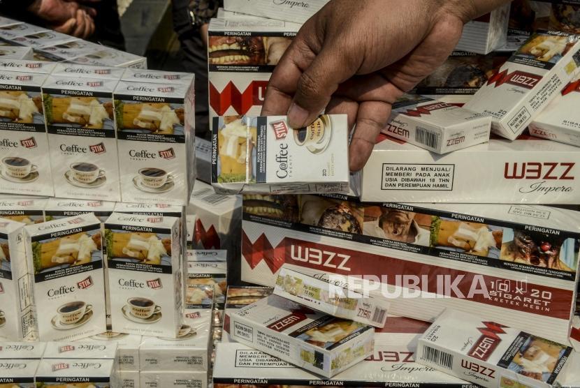 Petugas memperlihatkan bungkus rokok hasil penindakan barang kena cukai saat konferensi pers di Jakarta, Jumat (25/10).