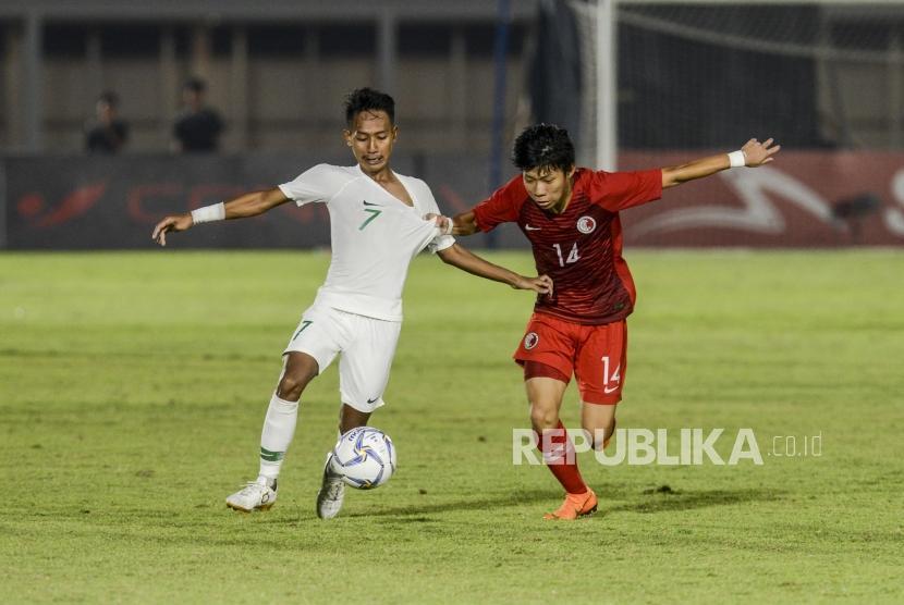 Pesepakbola Timnas Indonesia Beckham Putra Nugraha (kiri) berebut bola dengan pesepakbola Timnas Hongkong Cheng Chun Wang Ryan pada pertandingan kualifikasi AFC U-19 di Stadion Madya, Jakarta, Jumat (8/11).
