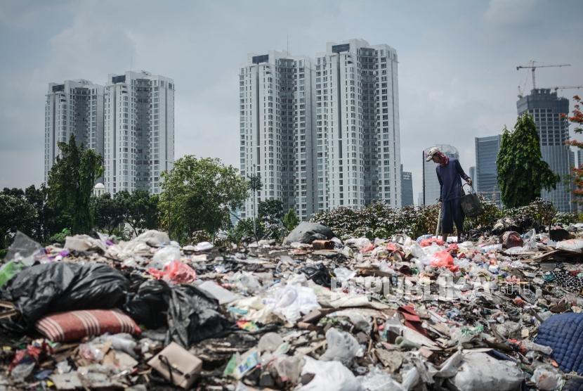 Warga memungut sampah dengan latar gedung-gedung di tempat penampungan barang rongsoki Kampung Gasong, Menteng Pulo, Jakarta, Selasa (17/12).