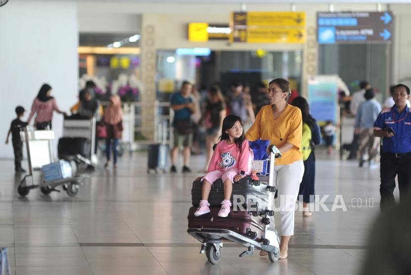 Penumpang pesawat udara membawa barang bawaan di Terminal Domestik Bandara Internasional I Gusti Ngurah Rai, Bali, Kamis (19/12). Pembangunan LRT Bali akan dilakukan Nindya Karya beserta Korea Rail Network Authority