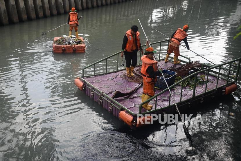 Petugas UPK Badan Air Dinas Lingkungan Hidup DKI Jakarta membersihkan sampah di Kali Cideng, Jakarta, Senin (30/12).