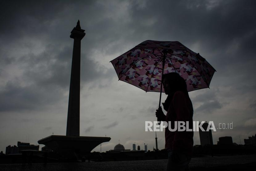 Sejumlah warga melindungi badannya dari air hujan dikawasan Monas, Jakarta (ilustrasi)