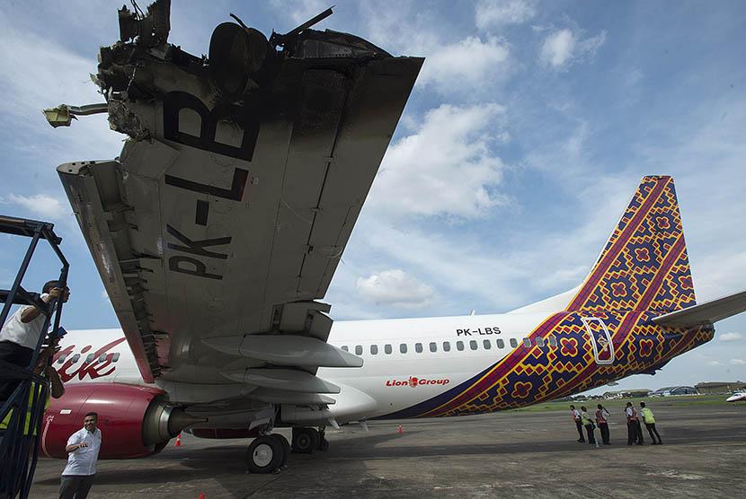 Sejumlah petugas mengamati bagian sayap kiri dari pesawat Batik Air dengan nomor registrasi PK-LBS yang mengalami insiden di Bandara Halim Perdanakusuma, Jakarta, Selasa (5/4). (Antara/Widodo S Jusuf)