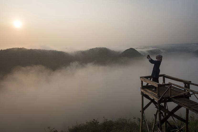Wisatawan menikmati suasana matahari terbit di Bukit Panguk, Kediwung, Mangunan, Yogyakarta. ilustrasi (Antara/Sigid Kurniawan)