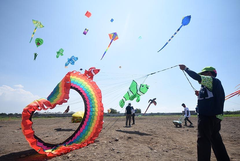 Seorang peserta berusaha menerbangkan layang-layang saat Surabaya International Kite Festival 2016 di Surabaya, Jawa Timur, Ahad (24/7). (Republika/M Risyal Hidayat)
