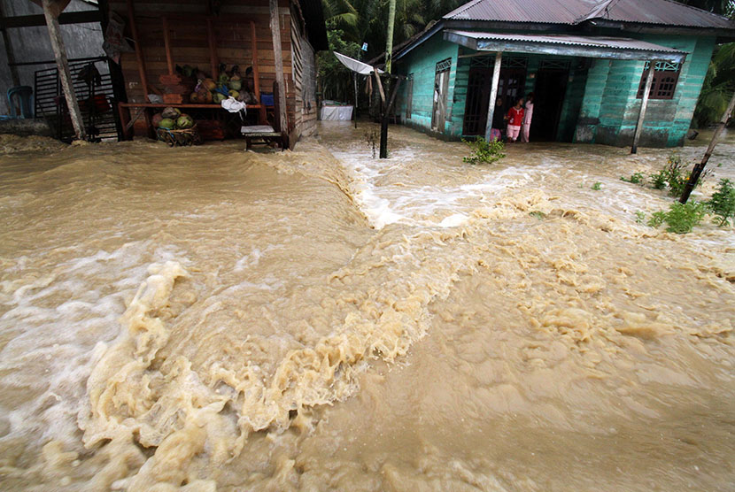 Warga berdiri di teras rumahnya yang terendam banjir. ilustrasi