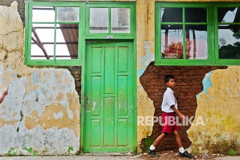 Seorang siswa SD melintas di depan ruang kelas yang rusak (ilustrasi)