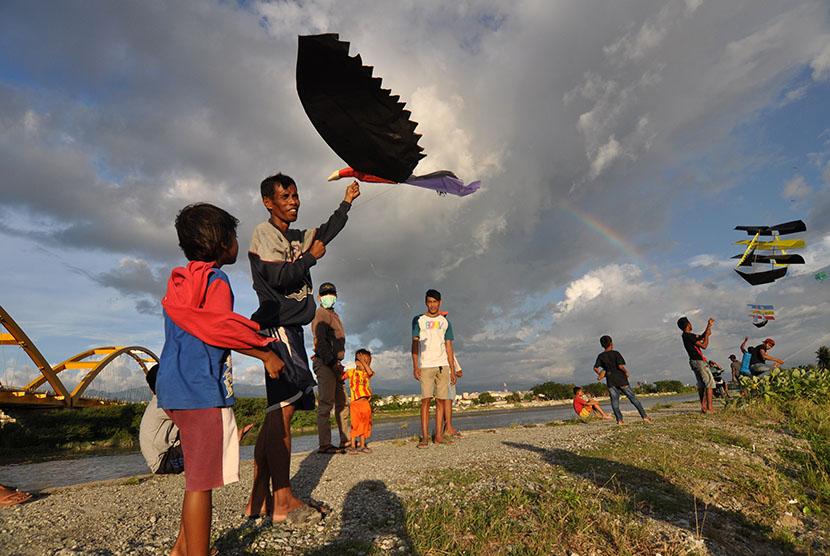 Sejumlah warga bermain layang-layang sambil menunggu saat berbuka puasa (ngabuburit) di sekitar Muara Sungai Palu, Sulawesi Tengah, Sabtu (27/5).
