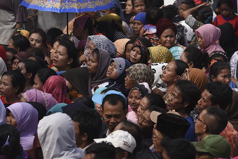 Warga mengantre pembagian zakat mal di Kawasan Ampel, Surabaya, Jawa Timur, Jumat (23/6).