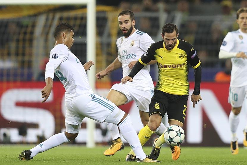 Pemain Real Madrid Casemiro (kiri) berusaha menghalangi pemain Dortmund Gonzalo Castro (kanan) pada pertandingan grup H Liga Champions di Dortmund, Selasa (26/9).