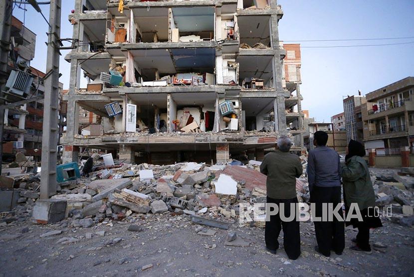 Warga menyaksikan bangunan yang hancur akibat gempa di kota Sarpol-e-Zahab, Iran, Senin (13/11).