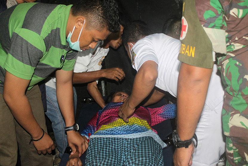 Petugas medis memeriksa warga yang berhasil dievakuasi Satuan Tugas Terpadu Penanganan Kelompok Kriminal Bersenjata setibanya di Timika, Papua, Jumat (17/11).