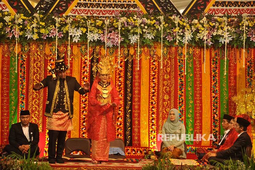 Putri Presiden Joko Widodo, Kahiyang Ayu (tengah) bersama suaminya Bobby Afif Nasution (kedua kiri) menari tor-tor Somba (pengantin) di depan kedua orangtua mereka ketika resepsi ngunduh mantu pernikahan mereka di Medan, Sumatera Utara, Sabtu (25/11).