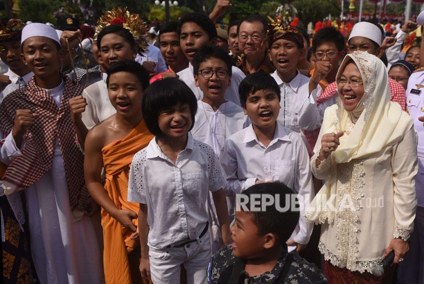 Walikota Surabaya Tri Rismaharini (kanan) menyapa sejumlah anak yang mengikuti upacara hari jadi Kota Surabaya ke-725 di Taman Surya, Surabaya, Jawa Timur, Kamis (31/5).