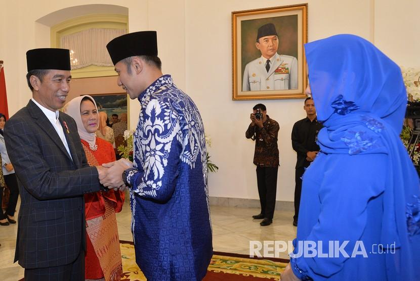 Presiden Joko Widodo (kiri) dan Ibu Negara Iriana Joko Widodo (kedua kiri) berjabat tangan dengan Politisi Partai Demokrat Agus Harimurti Yudhoyono (kedua kanan) dan isteri Anissa Pohan (kanan) di acara Silahturahmi Idul Fitri 1 Syawal 1439 H di Istana Kepresidenan Bogor, Jawa Barat, Jumat (15/6).