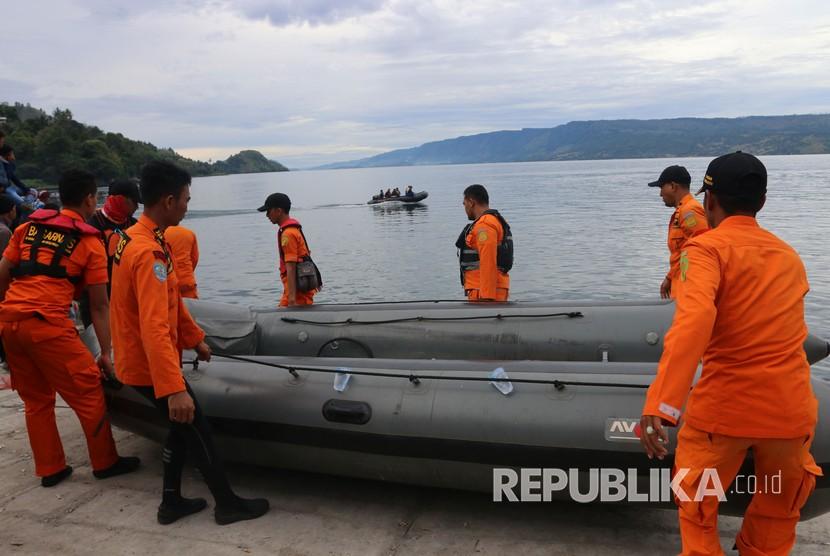 Personel Basarnas mengangkat perahu karet saat akan melakukan pencarian korban KM Sinar Bangun yang tenggelam di Danau Toba, Simalungun, Sumatera Utara, Rabu (20/6).
