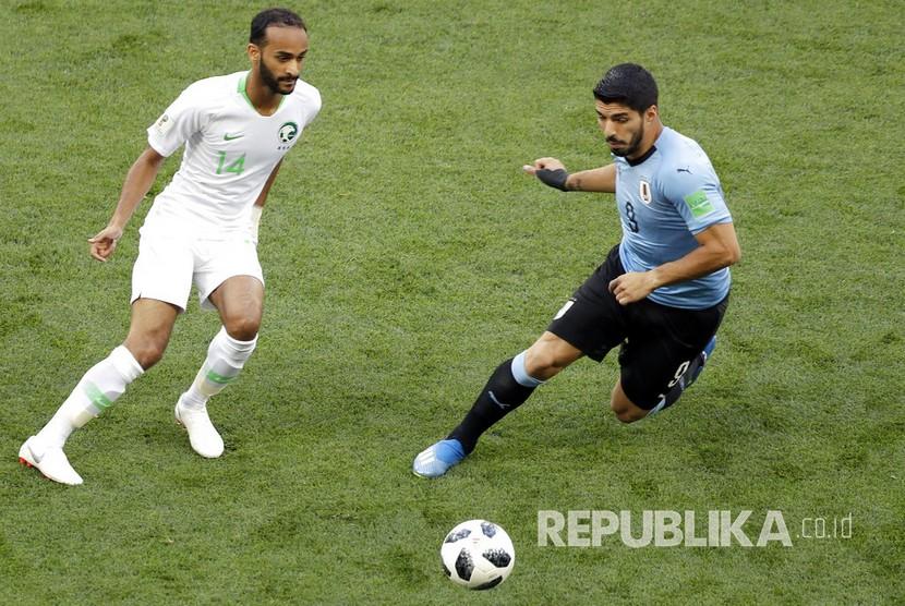 Luis Suarez berebut bola dengan pesepak bola Arab Saudi Abdullah Otayf pada pertandingan grup A Piala Dunia 2018 di Rostov Arena, Rostov na Donu, Rabu (20/6).