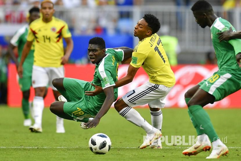 Pesepak bola Senegal Ismaila Sarr terjatuh dan dibayangi pesepak bola Kolumbia Johan Mojica pada pertandingan grup H Piala Dunia 2018 di  Samara Arena, Kamis (28/6).
